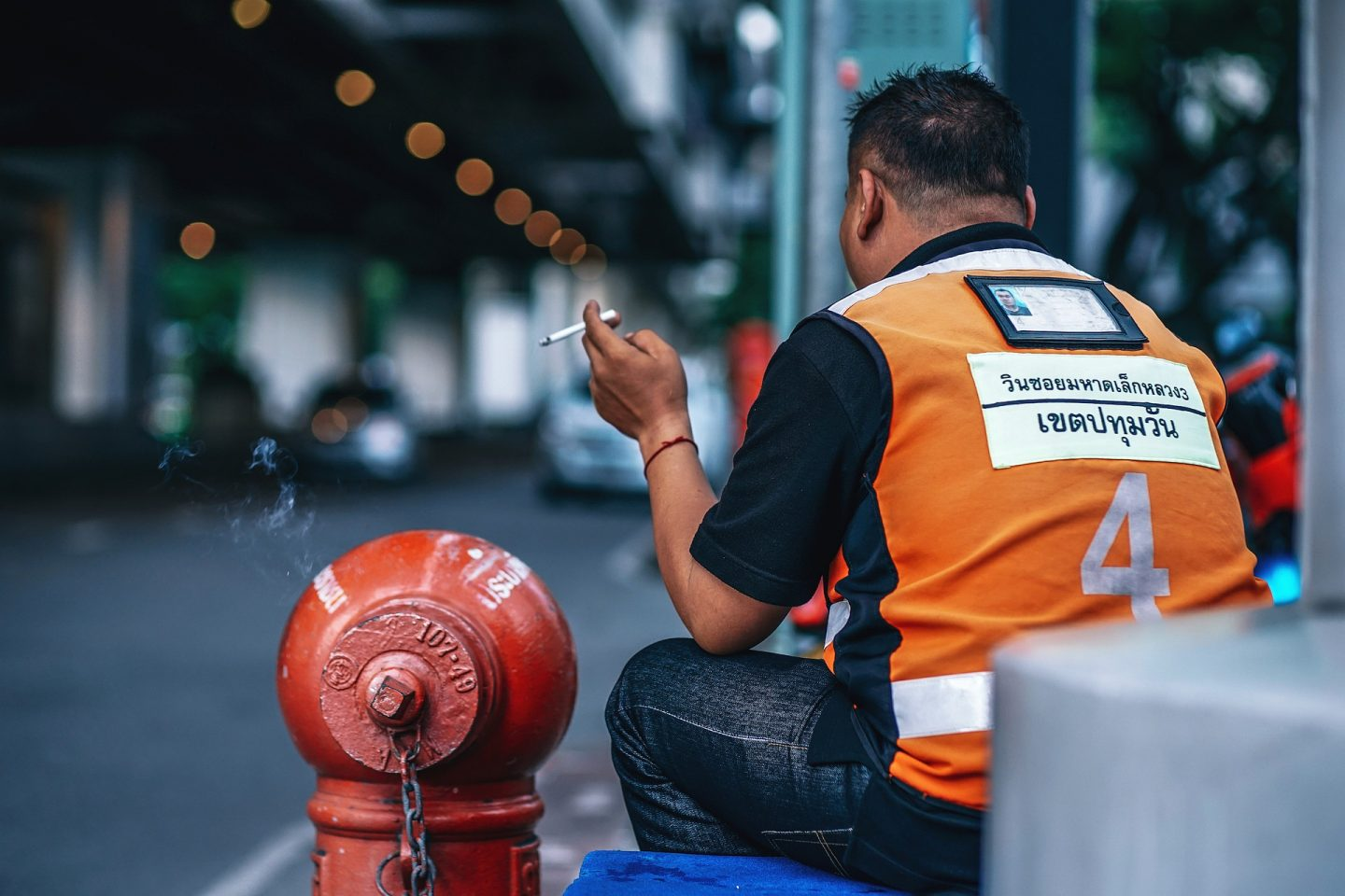 Motorcycle taxi driver smoking a cigarette
