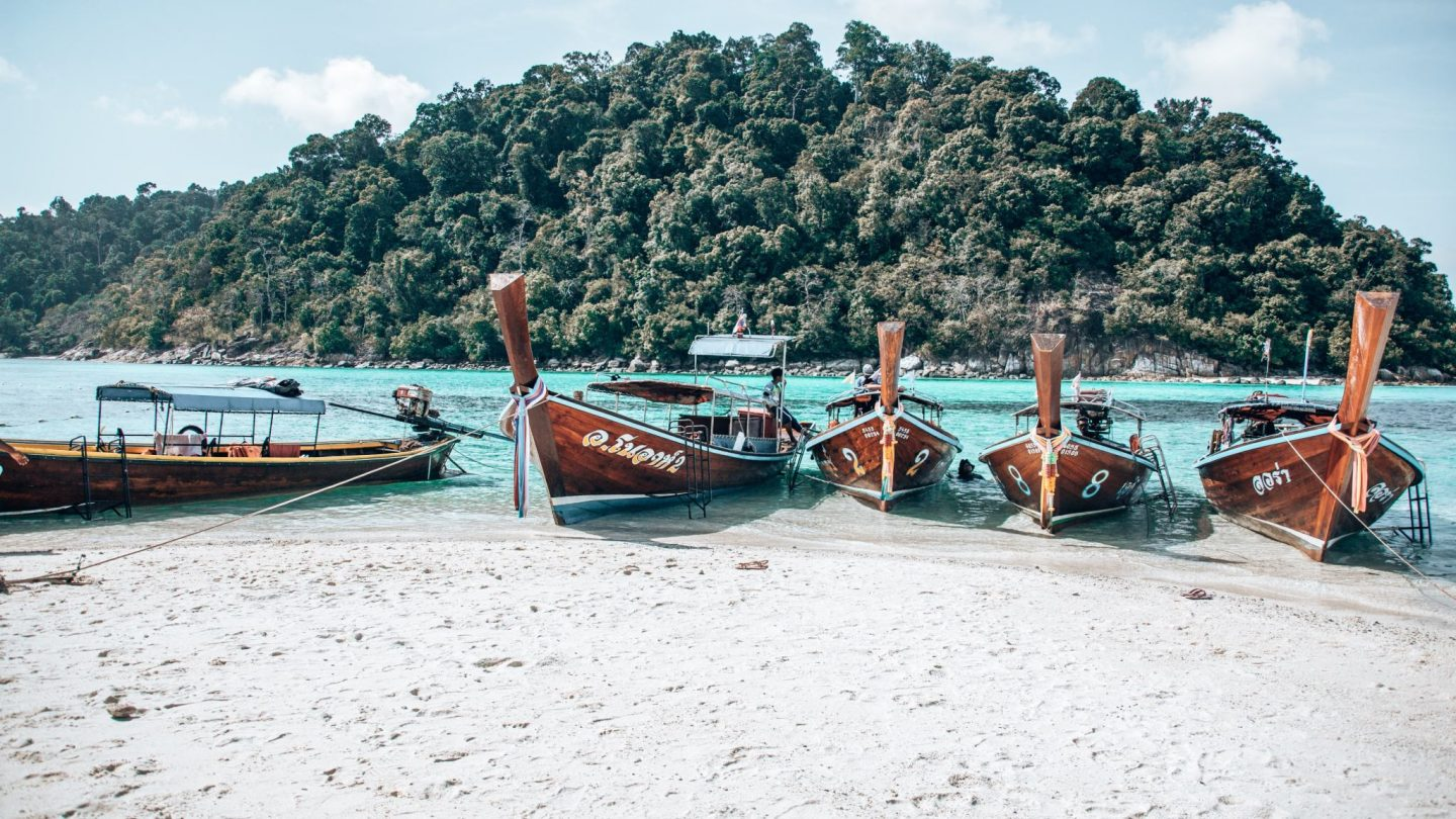 Longtail Boats on a white sandy beach with brilliant turquoise water behind.