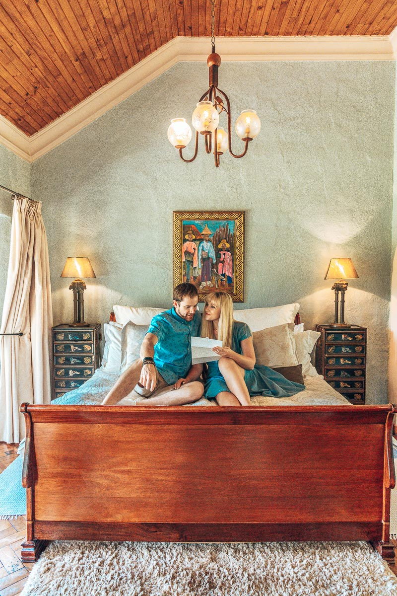 Byron & Tammy sitting on the bed in a Hartford House Suite