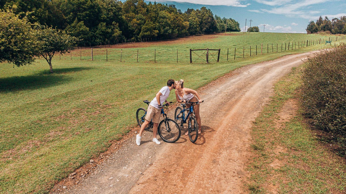 Byron & Tammy kissing while riding bicycles at Hatford House