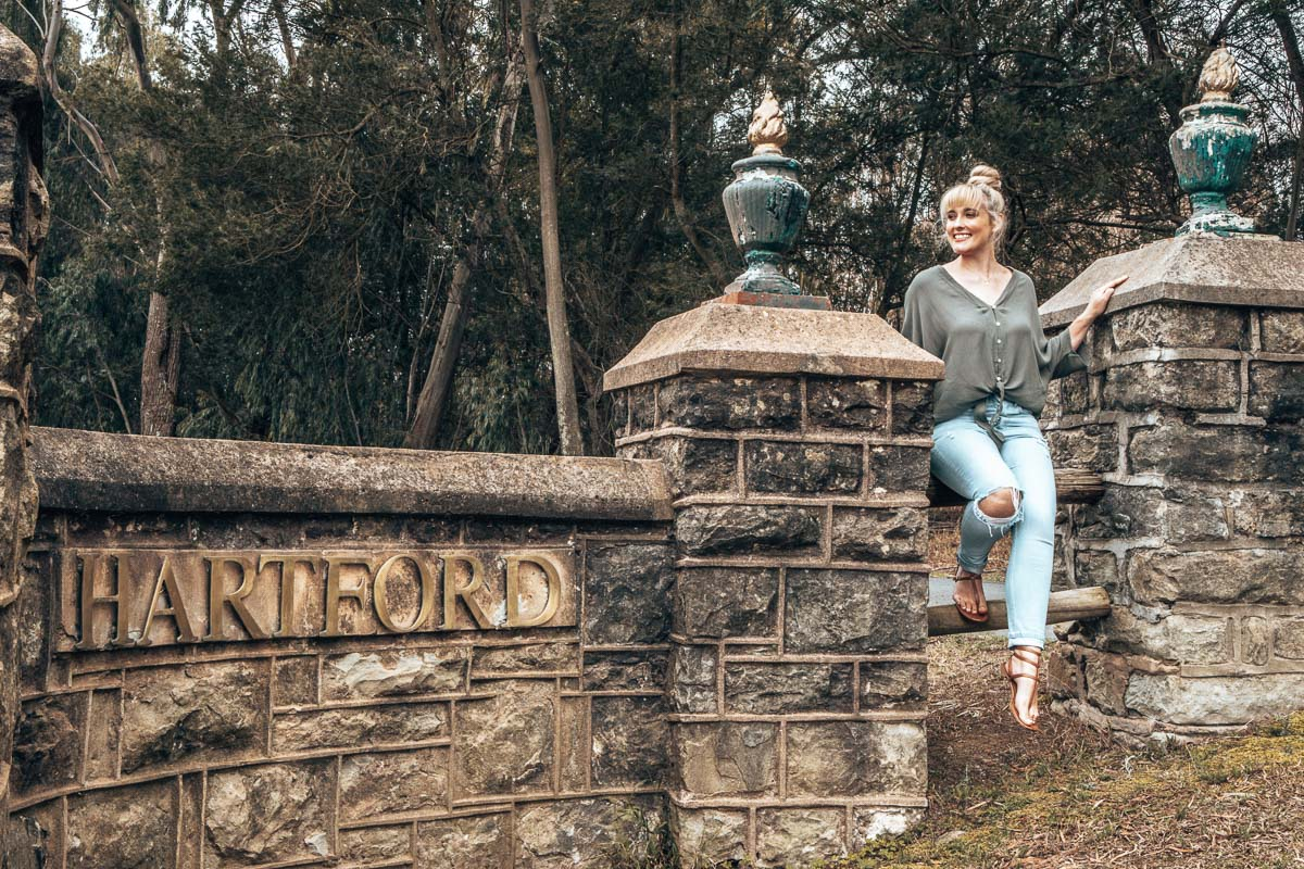 Tammy sitting on the Hartford House entrance gate