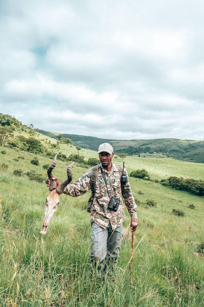 Mbuyiseni holding a buck skeleton