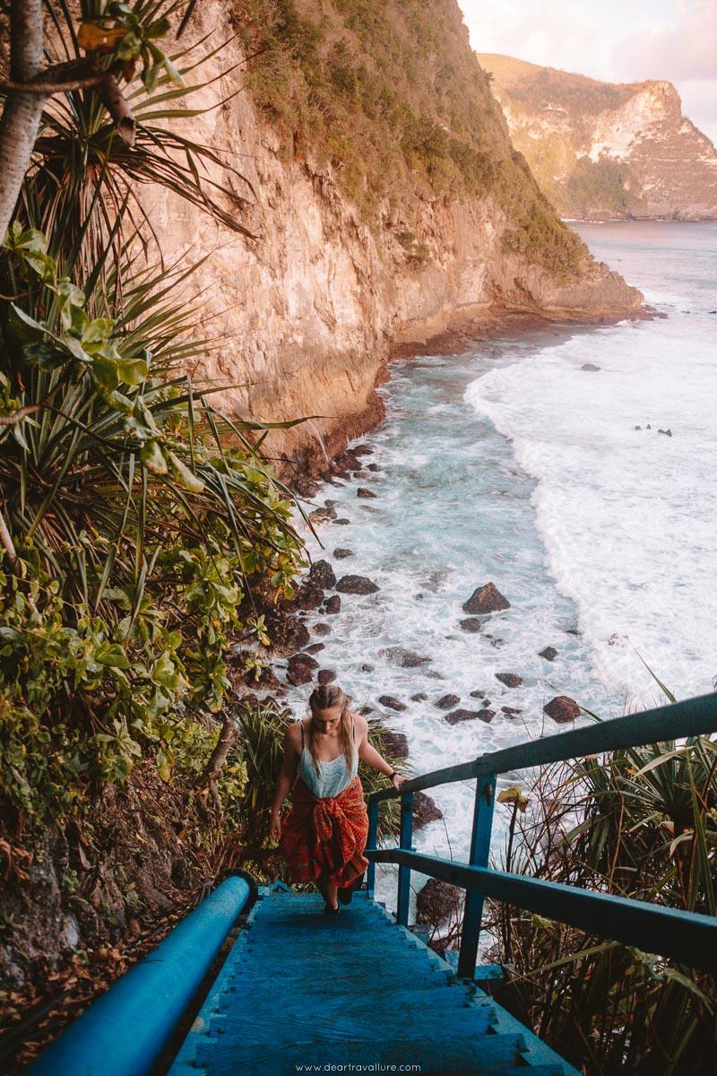 Girl walking up Peguyangan Waterfall's Blue Staircase