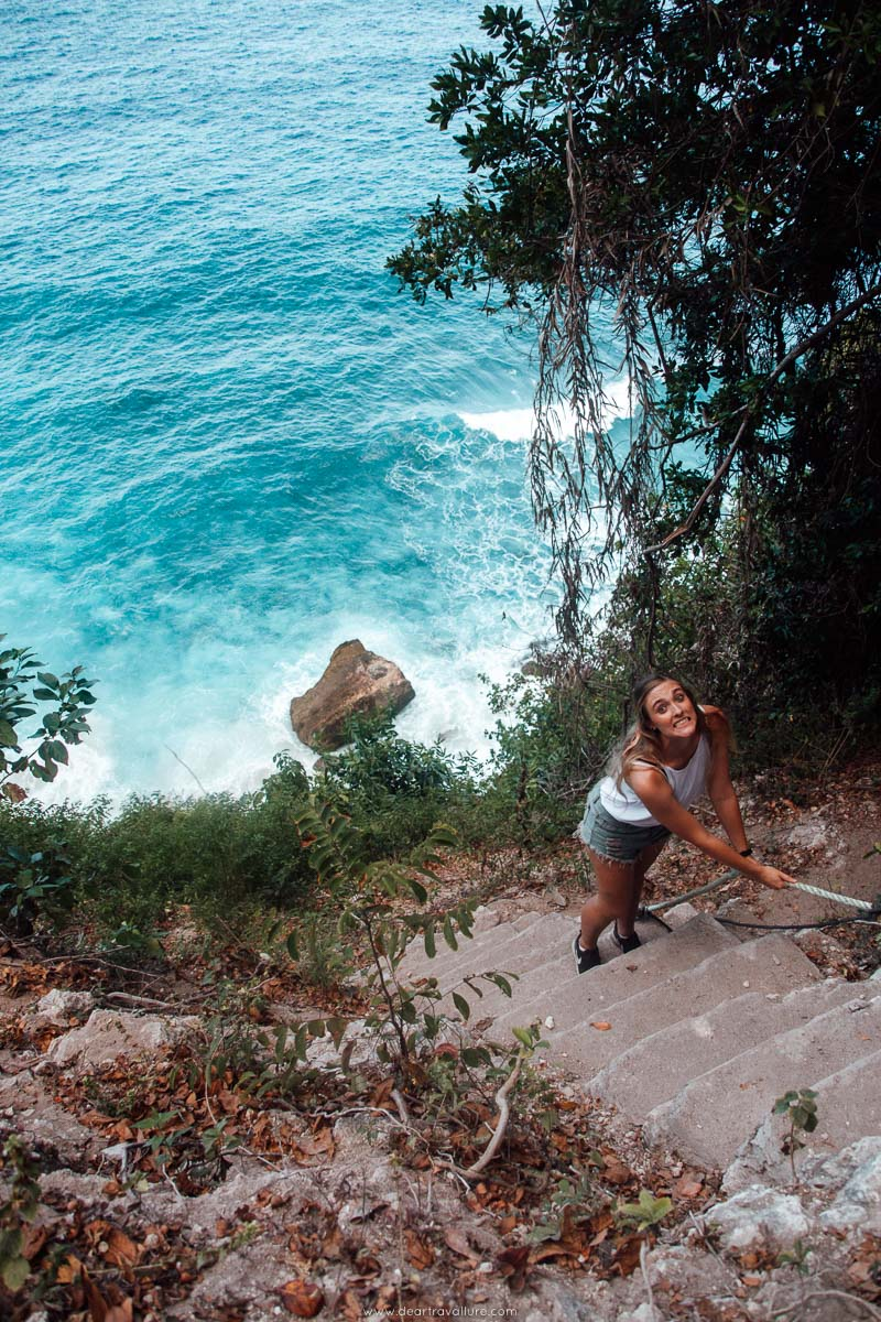 Climbing down the broken stairs at Suwehan Beach with bright blue waters below