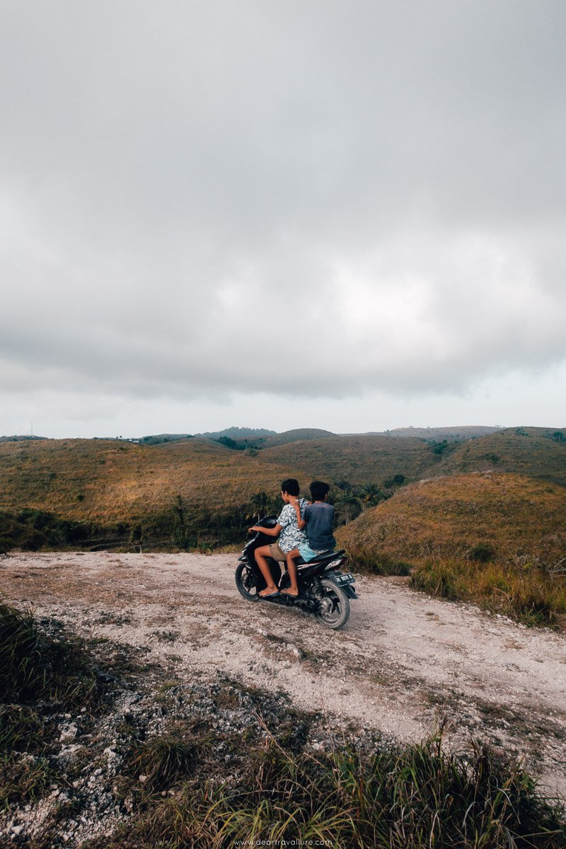 Two Young Local Kids Sharing A Scooter Near Teletubbies Hill