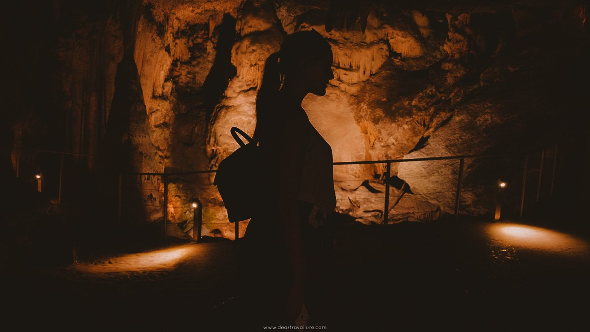 Silhouette of girl against backlight caves.