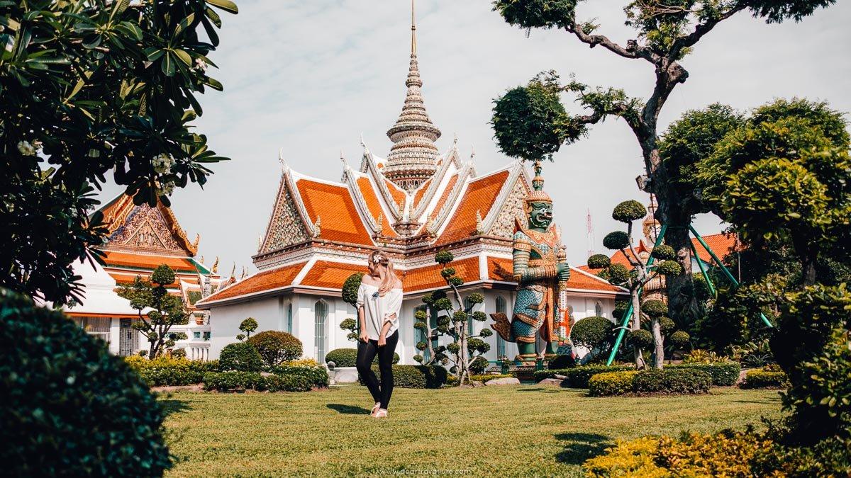a girl walking around the gardens of Wat Arun