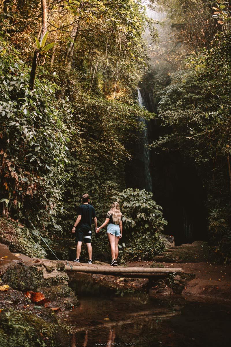Couple walking across the bridge at Pengempu Waterfall