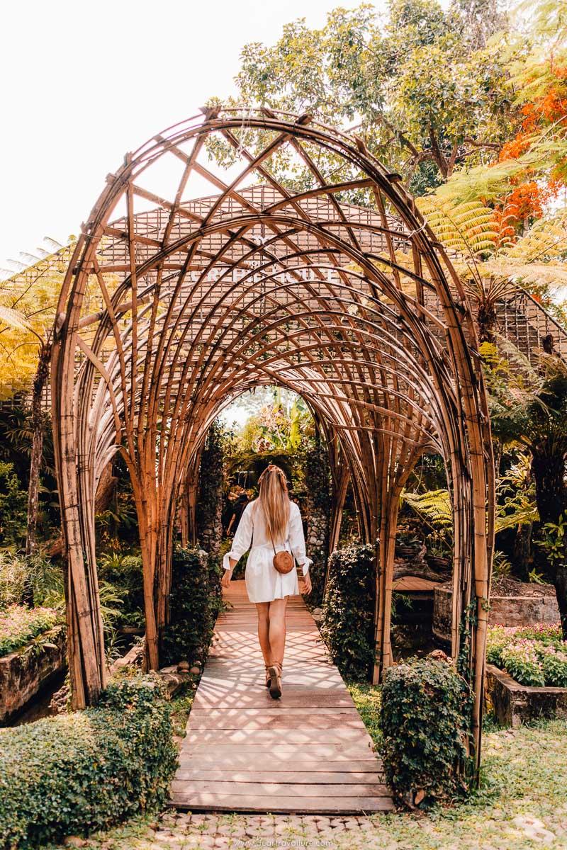 Tammy walking through a bamboo archway at Mae Fah Luang Gardens