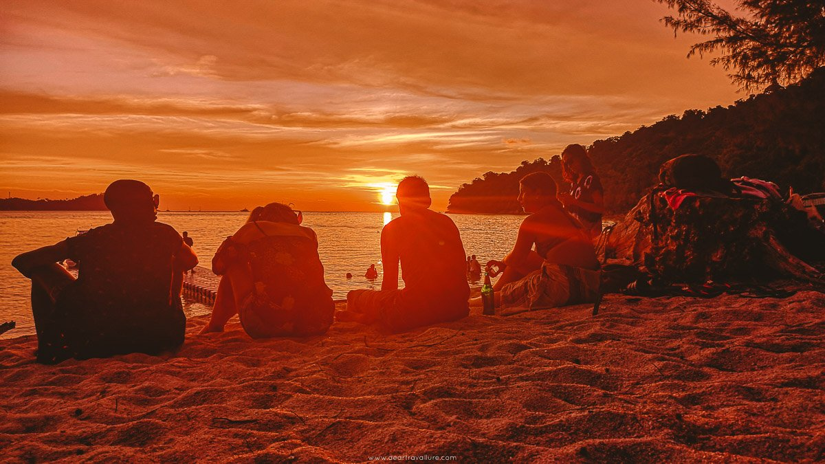 5 Friends sitting on the beach enjoying a beautiful sunset