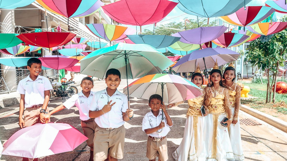 Students posing under colourful umbrellas