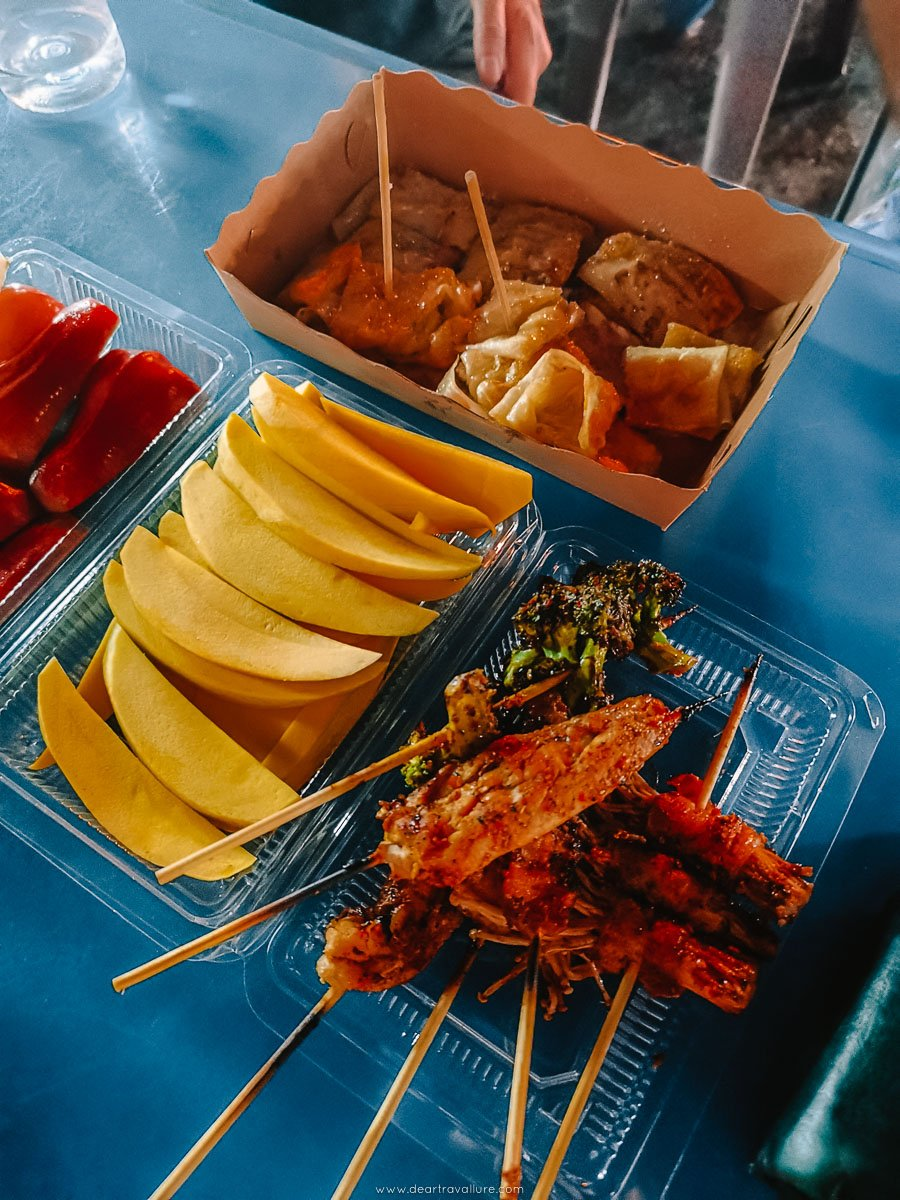 A selection of mango slices, chicken and veggies on a stick and banana roti