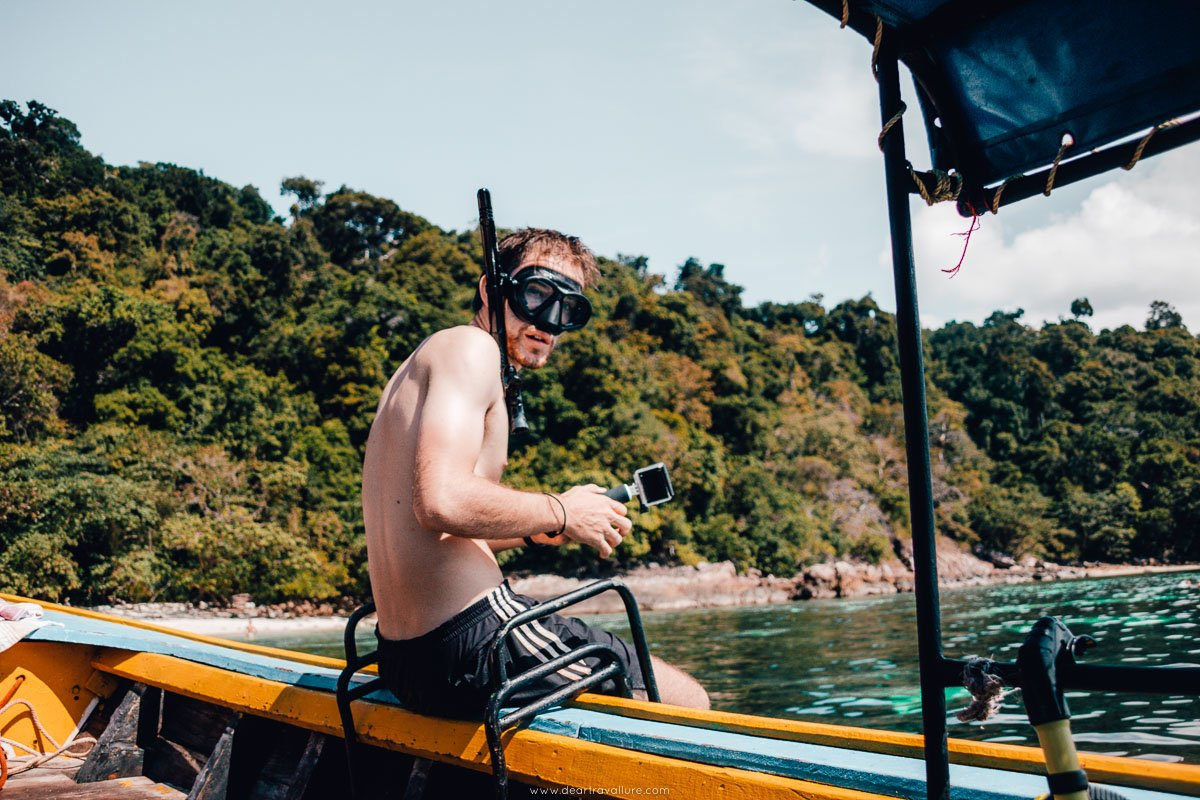 Byron sitting on the boats edge with a snorkelling mask on.