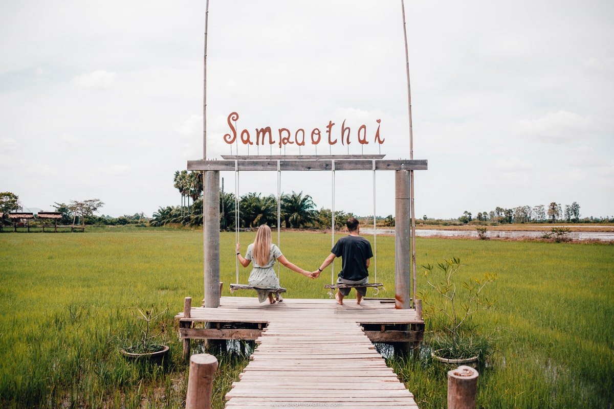 Byron and Tammy holding hands on the swings at Samphaothai