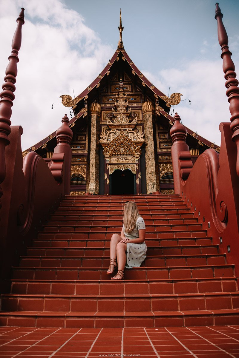Tammy sitting on the steps to the pavilion in the royal park rajapruek