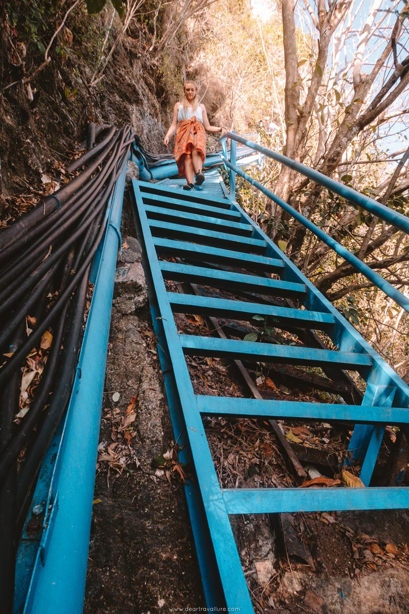 Climbing down steep stairs at Peguyangan Waterfall