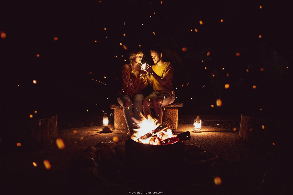 Byron and Tammy sitting around a campsite as embers surround them