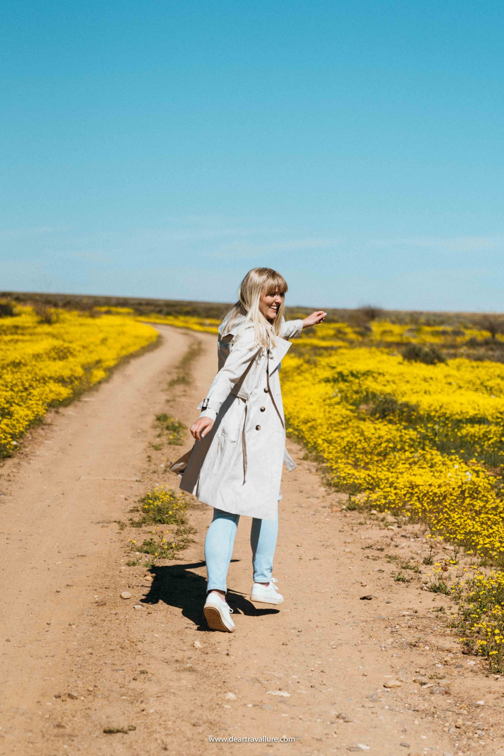 Tammy running along a dirt road amidst yellow flowers